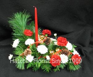 An oblong Christmas centrepiece with a red candle, pine cones, pine, carnations, ribbons, gold balls, and Icecap chrysanthemums.