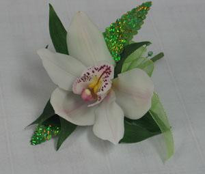 A single white cymbidium orchid with iridescent green leaves. This is a stunning and modern approach to the corsage or boutonniere.