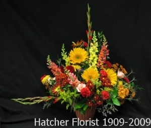 An arrangement of late Summer, early Fall flowers. We use a terra cotta look plastic container. This is a large display of flowers.