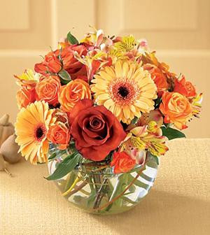 A glass cube holds gerbera, roses, alstroemeria, and assorted greenery.