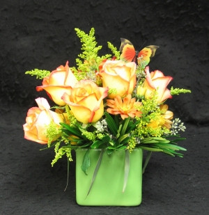 The growers in Holland named this rose Konfetti. Glass cubeor in a  green ceramic cube with roses solidago and hardy chrysanthemums nestled into the arrangement to add depth.