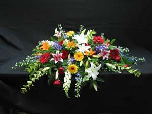 A casket spray for an open casket. Blue Delphinium, red and yellow Gerbera, white Siberia Lilies, pink Star Fighter Lilies, white Snapdragons, mixed foliage, orange Asiatic Lilies, and vibrant red Roses.