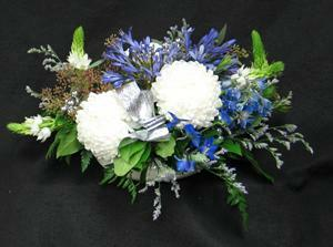 Long lasting Commercial Mums, blue Agapanthus, Ornithogalum, blue Delphinium, and seasonal greenery. A silver bow for accent.