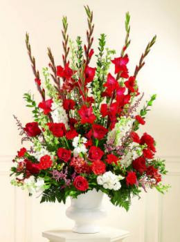 A traditional piece, this arrangement of red carnations, red roses, white Stock and or Snapdragons, larkspur with pink filler flowers in a white plastic urn is perfect for any ceremony where you need a large floral display.