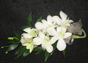 A lovely corsage with white dendrobium and dark green Italian ruscus foliage; gold ribbon. This is a pin on variety. We have a magnet that will save your dress, just ask.