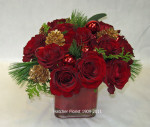 A group of 12 red Freedom roses in a glass cube with pine, fir, gold cones, red glass balls will brighten any office or home setting. The red roses are so rich against the pine and gold cones.