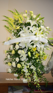 A large white and yellow standing spray made by Hatcher Florist. Snapdragons, orchids, gerbera, carnations and large white Oriental Siberia lilies.