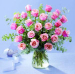 Striking. 24 beautiful long stem pink roses arranged in glass vase. We use mixed foliage and eucalyptus.