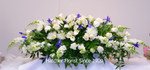 A blue and white flower casket spray. A peaceful combination of lilies, roses, snapdragons, and blue iris.