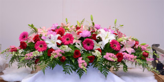 A stunning display of pink snapdragons, roses hot pink gerbera, red freedom roses and white oriental liles. this is a spray for a closed casket. Made exclusively in our flower shop. toronto and GTA area deliveries.