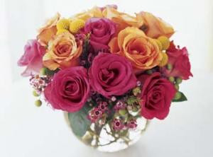 Vibrant color roses burst from a glass bowl. Hot pink roses, orange roses, and two-tone orange and pink roses converge with deep pink waxflower. This bold bouquet is a treat to behold. In a rose bowl. We can deliver today for you.