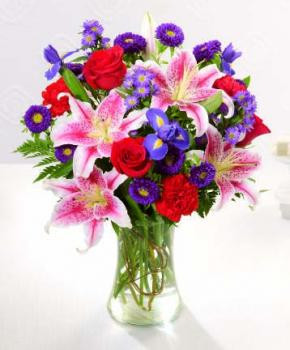 A vase arrangement with its array of red roses, pink Star Gazer lilies, purple Irises, purple aster and more.