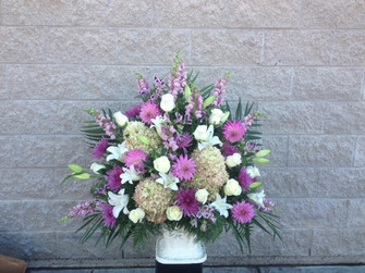 Pastel mixed flowers including PeeGee hydrangea, white oriental lilies, mauve snapdragons, pinky mauve dahlias and alstromeria. A quiet sentiment for any funeral floral offering of you sympathy. We can design one for you in our Toronto and North York area flower shop. Selling flowers in Toronto for over 100 years.