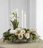 The FTD® Glowing Elegance™ Centerpiece is a departure from the everyday arrangement, stepping into a design blooming with modern sophistication. Exquisite white roses and standard carnations are brought together with assorted holiday greens and seeded eucalyptus at the base of the arrangement accented by copper glass balls and a gold glitter ribbon. Blooming from the base is a spray of white narcissus stems standing next to 2 white taper candles for an eye-catching look that will lend itself to making your holiday festivities both merry and bright.
