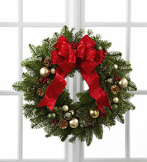 The FTD® Winter Wonders™ Wreath showcases the festive feelings and holiday cheer of the season. Comprised of assorted holiday greens this wreath is accented with gold pine cone pics, berry pics, assorted green glass balls, opalescent pearl glass balls and matte gold glass balls culminating in a brilliant red ribbon tied at the top to create an incredible wreath to celebrate the Christmas season.