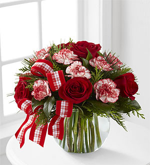 The FTD® Winter Elegance™ Bouquet offers warm wishes and bright sentiments for a wonderful holiday season! Rich red roses and peppermint carnations are delicately arranged amongst holiday greens to create a festive display. Arriving in a clear glass bubble bowl and accented with a red and white plaid ribbon, this arrangement is full of seasonal sophistication.