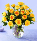 Bright yellow roses arranged in a vase with mixed greenery. We use hummer or Gold Strike roses.Sunny and bright 24 graceful yellow long stem roses are arranged with greens in a clear glass vase. Sunny enough for a celebration, but soothing enough for a Get Well or Sympathy gift. We do have other colours!
