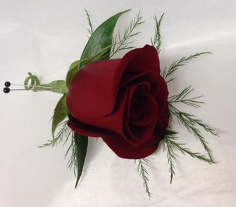 Classy classic red rose Boutonniere. We also do them in white, yellow, pink, purple/mauve and orange. The tikki fern adds a feathery touch. Call at least a week before you need your corsages and boutonnieres, please.