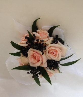 Sweetheart roses, ruscus, tulle and baby breath sprayed black. This was a custom design for specific dress. We made a matching boutonniere for the gentleman.