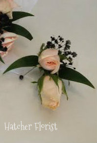 Soft flamingo pink boutonniere with ruscus, sweetheart roses and  black baby breath. Made to match the wristlet.