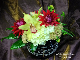 In a heavy keepsake bowl we have designed a mix of dahlias, sedum, hydrangea and cymbidium orchids. Grace any table at Rosh Hashanah or any Fall celebration with this lovely design.