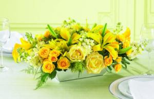 Perfect for any celebration, this golden centerpiece of yellow roses, yellow Asiatic lilies and creamy, fragrant Stock  or Snapdragons will bring a sophisticated touch to your table or buffet. Great for a Golden Wedding anniversary gift.