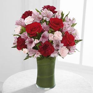 The Love in Bloom™ Bouquet is the perfect expression of sweet affection and adoration. Rich red roses, burgundy carnations, pink Peruvian lilies, pink mini carnations and lush greens are gorgeously arranged in a clear glass vase lined with a ti leaf to create a stunning way to convey your most heartfelt emotions.
