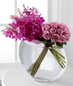Create harmony and peace in honor of the bond you share. This unique and fashionable bouquet bursts with our finest blooms. Brilliant violet Mokara Orchids are the perfect pairing to our lavender 24-inch premium long-stemmed roses brought together in a superior 13-inch clear glass pillow vase to express your heart's every wish.