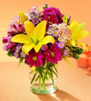 Celebrate Happy Times - past, present and future. Yellow Asiatic lilies and purple daisy poms are sprinkled with mini carnations and lavender monte casino and arranged in a clear glass vase. It's the perfect birthday gift!