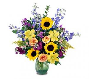An impressive presentation of flowers. A rainbow of colours in a glass vase. This arrangement is the perfect gift for any occasion with its Roses, Lilies, Sunflowers, and more.