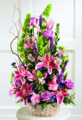 Superb Stargazer lilies with lavender roses, pink variegated carnations, and liatris with Bells of Ireland are arranged in a bamboo dish garden..