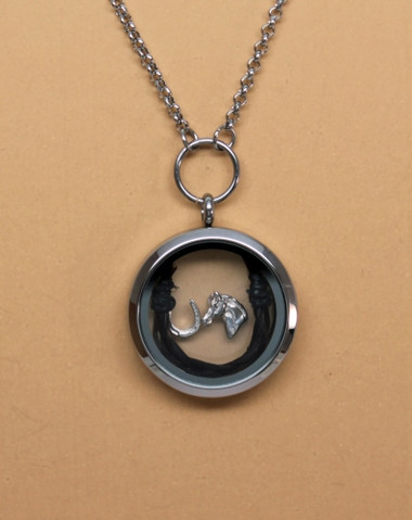 This memorial locket holds precious keepsakes and memories of your horse.The stainless steel and glass locket comes with 2 fine rubber bands which you can use to secure a braid of your horses mane or tail. Once put in the locket it forms a horseshoe shape. The locket also comes with a sterling silver horseshoe and horse head charm.The chain is 24 inches.