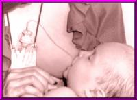 A baby nurses with the help of Lact-Aid System.