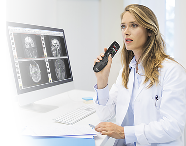 Female doctor in front of brain CAT scan using Philips SpeechMike Premium Air SMP4000 and Dragon Medical Practice Edition 4.