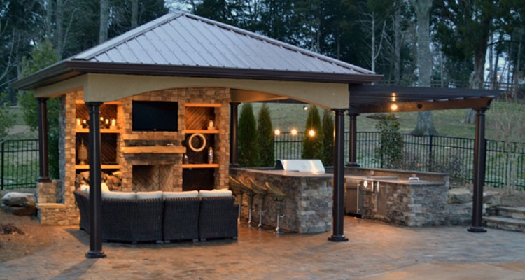 Outdoor pergola with couch, TV, barbecue, and outdoor fountain.