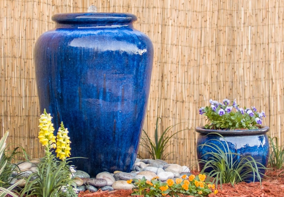 Outdoor blue bubbler fountain surrounded by flowers.