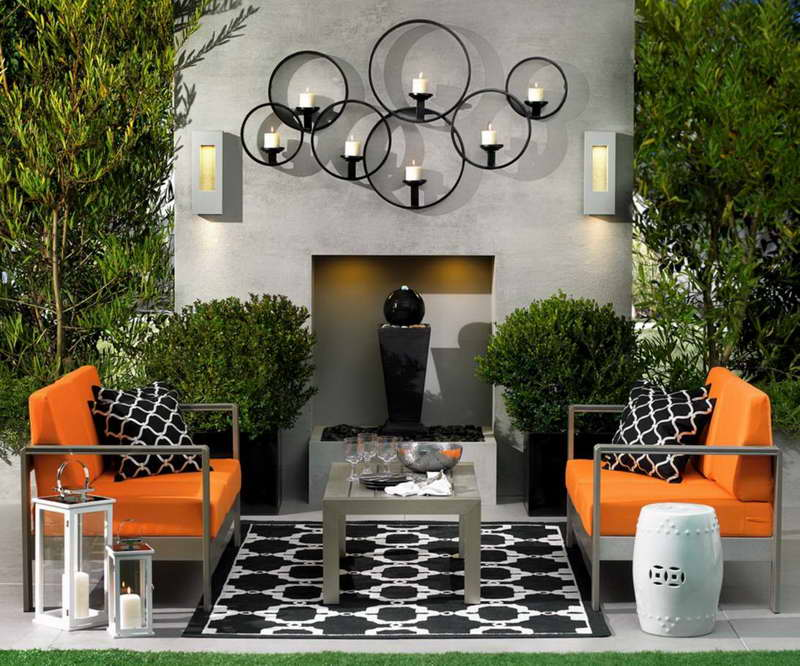 Backyard patio with furniture, decor, and black bubbling fountain.