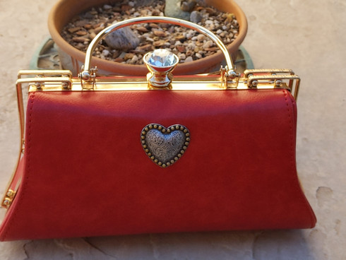 Red handbag with Western Style Heart. Fauz Red Leather. Gold Chrome Top Handle Hardware. Matching Crossbody Strap.  Large Enough for all smartphones and daily necessities.  From the Uptown Rodeo Rose Specialty Handbag Collection