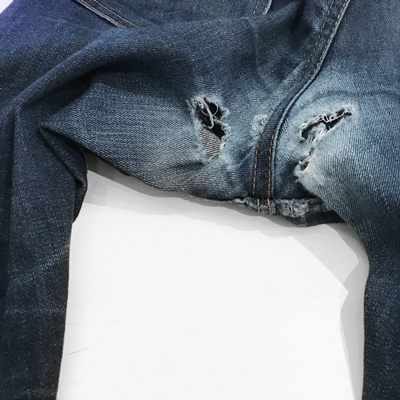 Faded and aged raw denim jeans with blown-out crotch