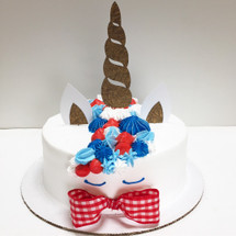 Decor includes: red/white/blue whipped cream frosting hand-piped, a custom Unicorn topper set by Blinged Baker, and a red checkered bow tie.