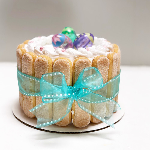 Cathy's classic holiday design for Easter. Featuring lady fingers around the cake wrapped like a package with a bow and non-edible Easter egg figurines on top.