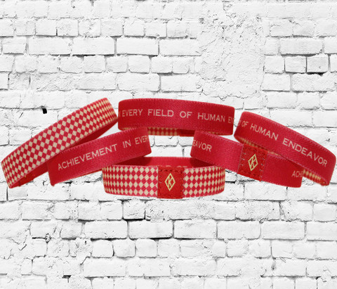 "Kappa Alpha Psi crimson and cream Poly-wristband. The ΚΑΨ wristband features diamond K and the fraternity motto ""achievement in every field of human endeavor"". The reverse side is a crimson and cream diamond pattern with the diamond K in center."