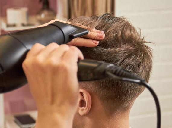Barber drying hair in salon after drying