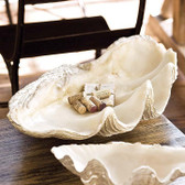 This large clam replica serves as a bowl or decorative object. Its resin construction beautifully mimics the details of a clam for a coastal feeling. Bring its shoreline style to a sideboard or coffee table in your living room.
