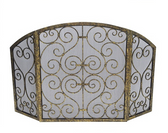 A gold scroll gate fireplace screen from Old World Design.