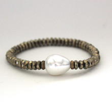 Pyrite with a Mother Of Pearl accent to promote clarity, clear thoughts and peace. Mix|Stack|Blend|Layer|Collect  Handmolded Brass Accent for natural good. Stretch Bracelet. 7 inches. Limited Quantities.