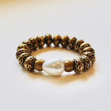 You know it's EVERYWHERE! 80's Vintage style is EVERYTHING now and it all yours with this bracelet featuring a light metal coating over lucite beads. Known for promoting peacefulness, the mother-of-pearl  accent brings it into TODAY with meaning...check it out!  Mix|Stack|Blend|Layer|Collect  Handmolded Brass Accent for natural good. Stretch Bracelet. 7 inches. Limited Quantities.