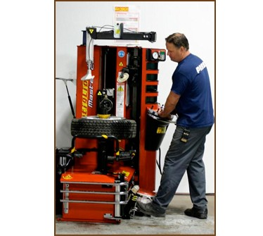 Tech using a tire changer/tire machine