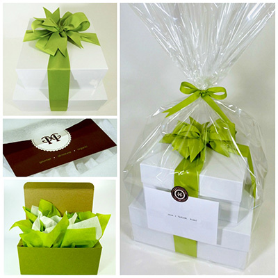 Two stacked white high gloss gift boxes tied with grosgrain ribbon