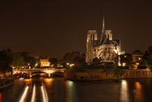 Nighttime at Notre Dame Cathedral from the Pont de la Tournelle bridge with boat traffic.